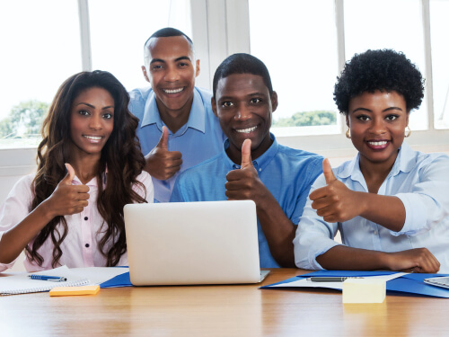 group of business people showing their thumbs up